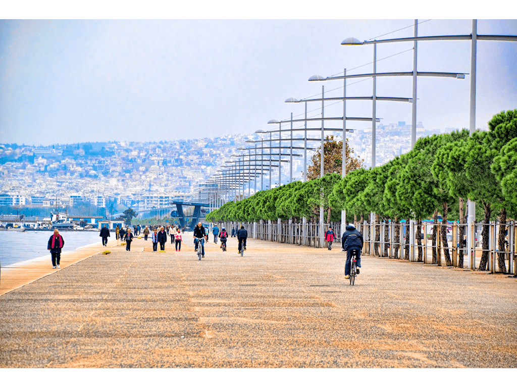 People walking and riding with bikes at the seafront